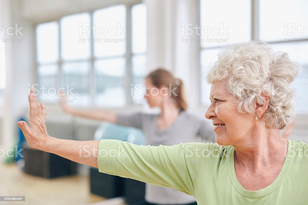 Senior woman doing stretching exercise at yoga class stock photo