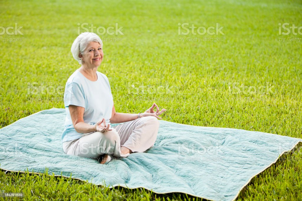 Senior woman doing yoga exercises stock photo