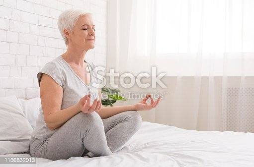 istock Senior woman doing yoga on bed at home 1136832013