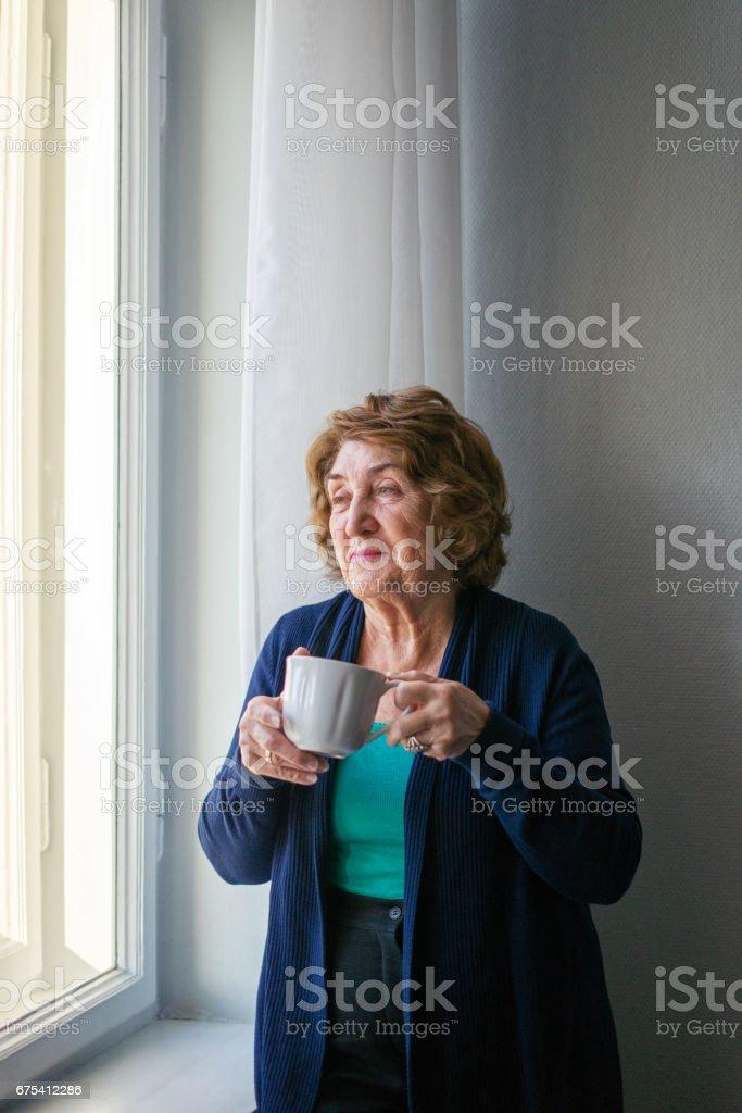 Pencerenin yanında kahve içme kadın kıdemli royalty-free stock photo