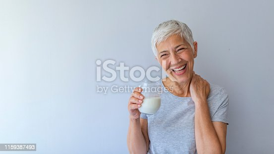 Cheerful mature woman having fun while drinking milk. Senior woman drinking from a clear glass full of milk. Woman in her golden age. Smiling, beautiful senior lady drinking a glass of milk