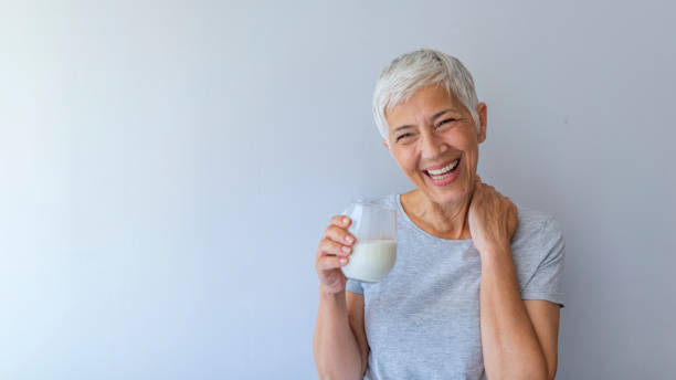 Senior woman drinking from a clear glass full of milk Cheerful mature woman having fun while drinking milk. Senior woman drinking from a clear glass full of milk. Woman in her golden age. Smiling, beautiful senior lady drinking a glass of milk 65 69 years stock pictures, royalty-free photos & images