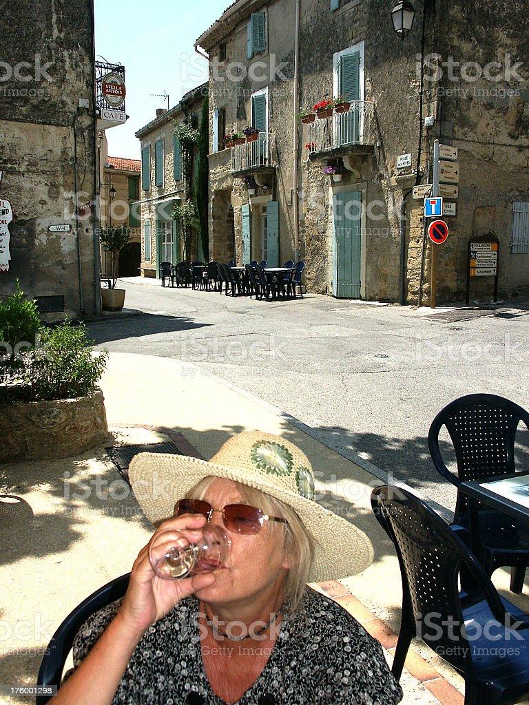 Senior woman drinking on a sunny french streetcorner royalty-free stock photo