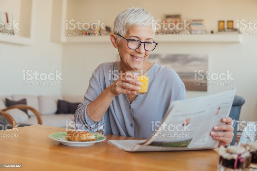Senior woman drinking orange juice at home foto stock royalty-free