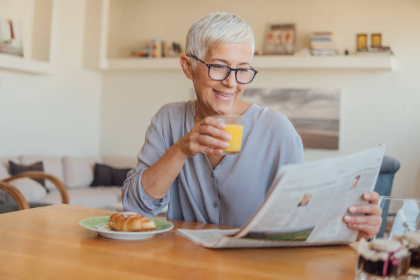 Senior woman drinking orange juice at home Elderly woman holding newspapers while having breakfast at home one mature woman only stock pictures, royalty-free photos & images