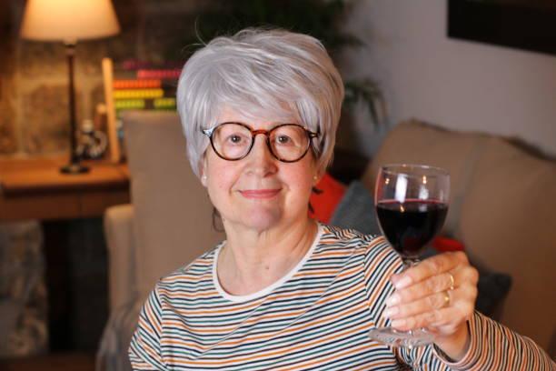 Mulher idosa bebendo vinho tinto - foto de acervo