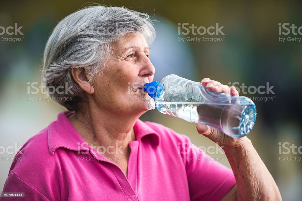 Senior woman drinking refreshing water from a bottle. stock photo