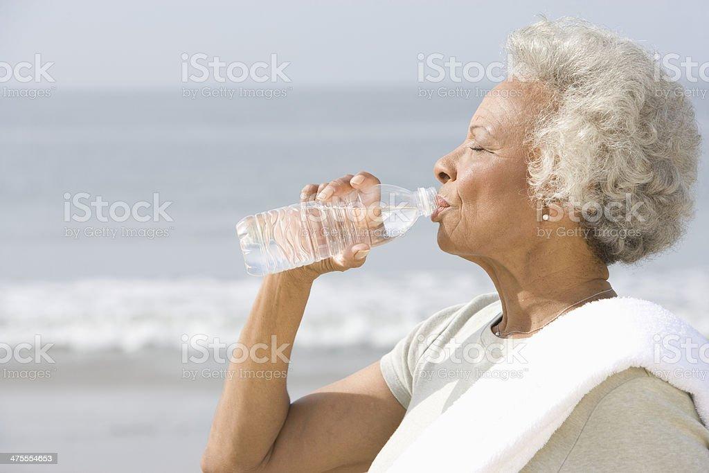 Mujer Senior bebiendo agua de botella en la playa - Foto de stock de Actividad libre de derechos