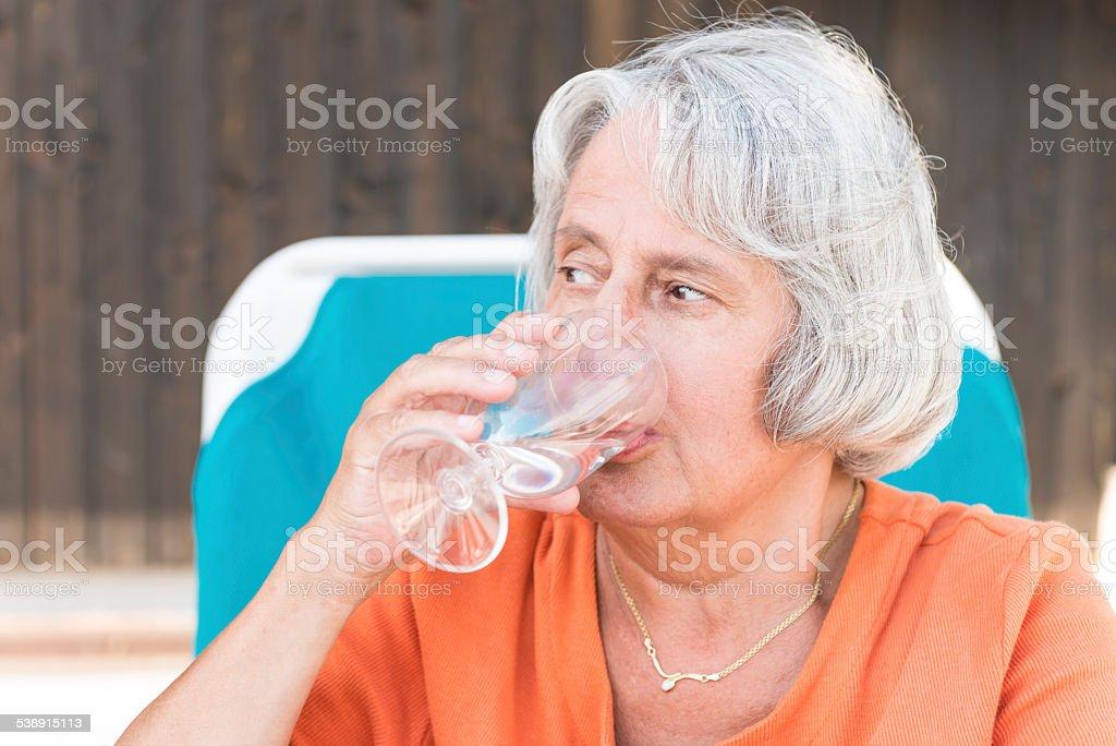 Senior woman drinking water stock photo