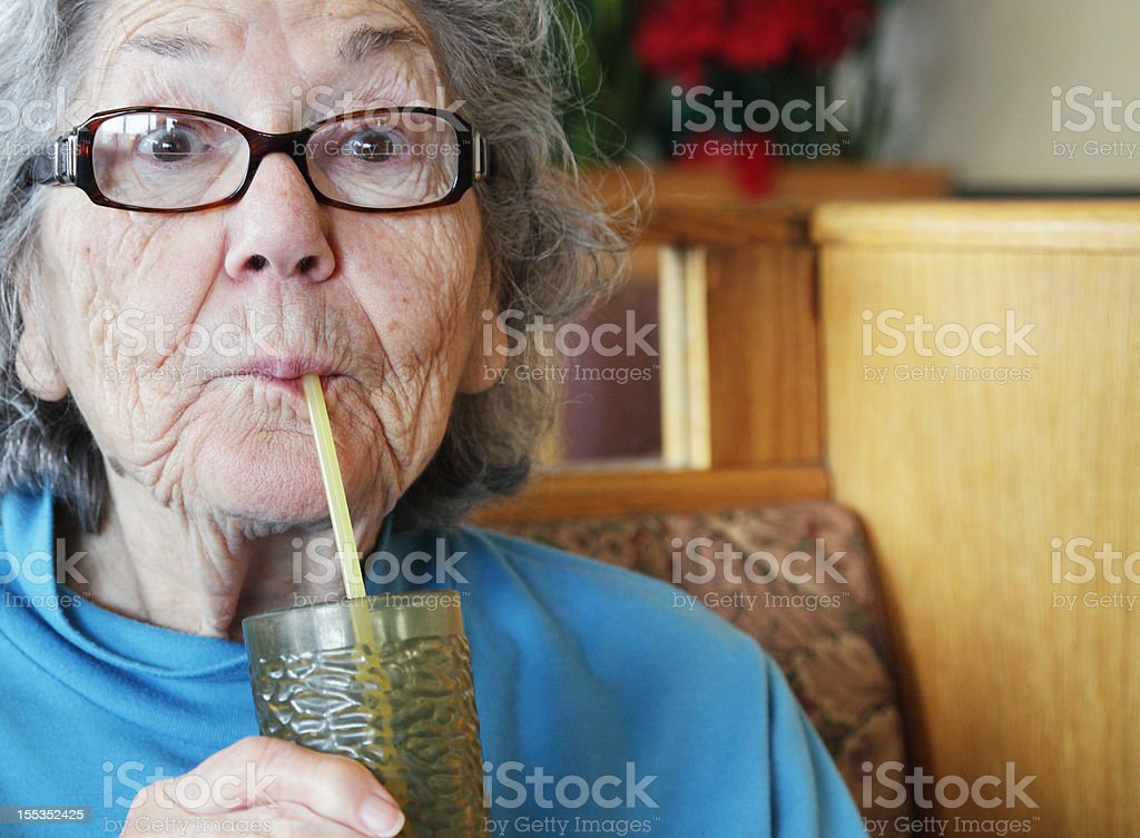 Senior Woman Drinking Water With Straw stock photo