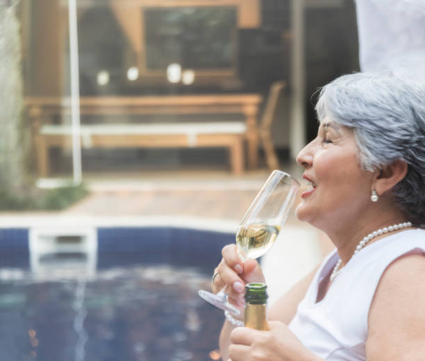 Senior woman drinking wine Senior woman  sitting by a swimming pool drinking a wine glass. Celebrating New Year`s Eve in Brazil. reveillon stock pictures, royalty-free photos & images