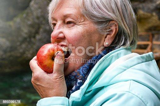 istock Senior woman eating apple 889399178