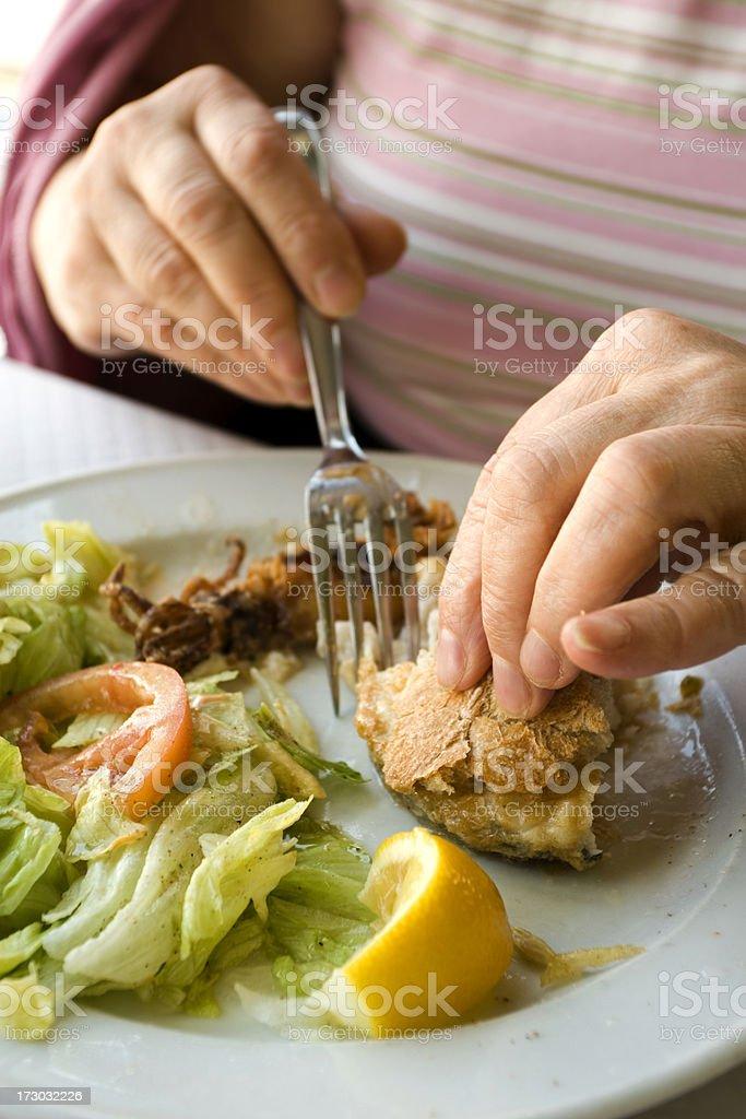 Senior woman eating fishfood and bread. royalty-free stock photo