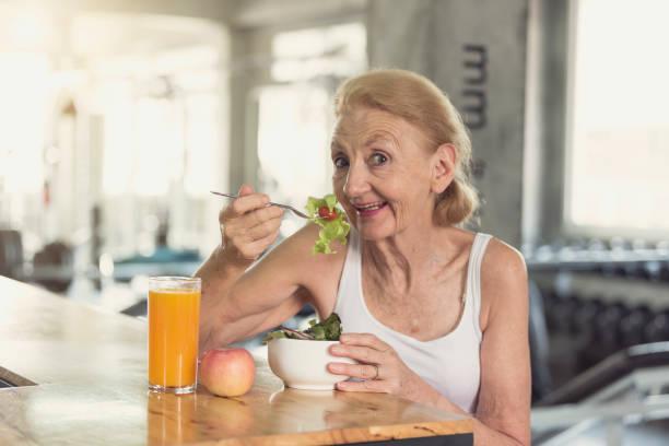 Seniorenfrau isst gesunden Salat und Orangensaft. Altenpflege Lifestyle Ernährungskonzept. – Foto