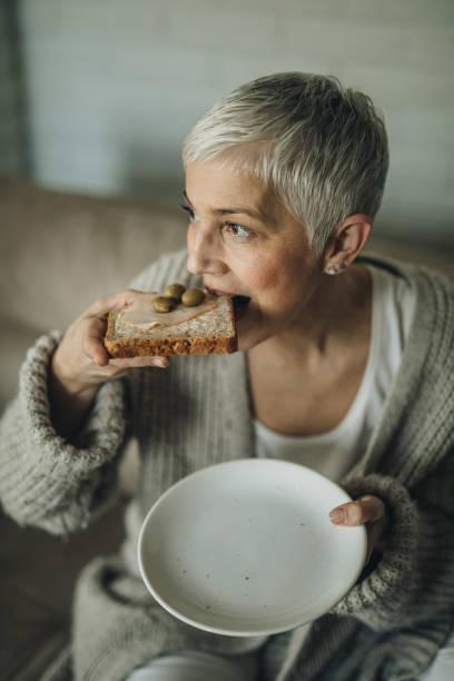 ältere frau sandwich für das frühstück zu hause zu essen. - oliven wohnzimmer stock-fotos und bilder
