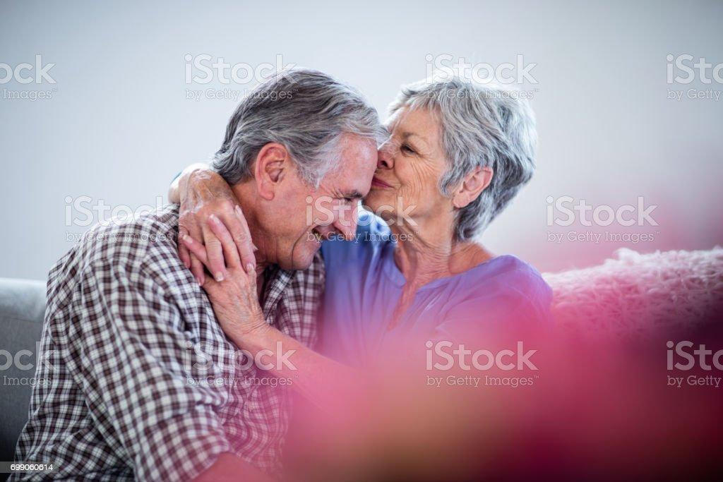 Senior mujer abrazándose y besándose en mans frente - foto de stock