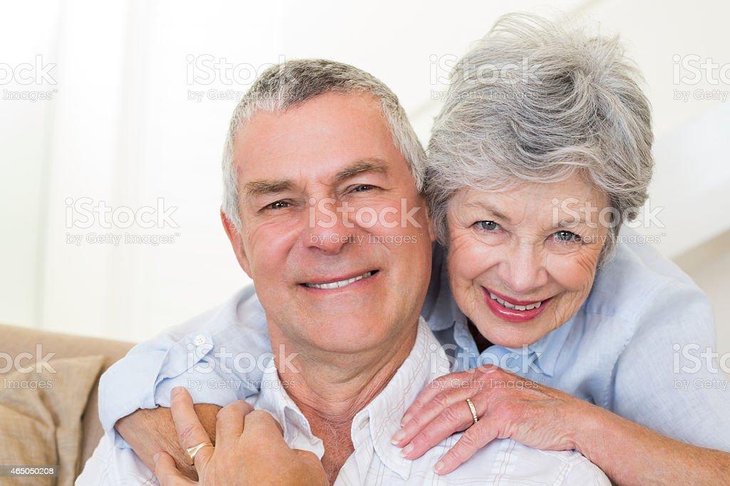 Senior woman embracing husband from behind stock photo