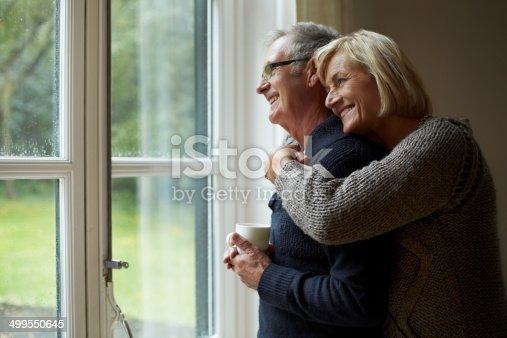 istock Senior woman embracing man in front of door 499550645