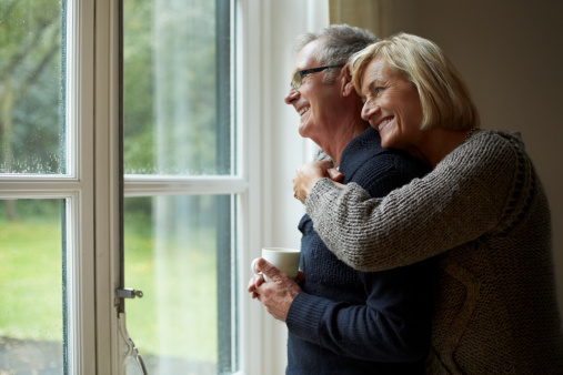 Senior woman embracing man in front of door