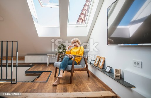 Senior woman relaxing with her digital tablet in a sky-lit cozy nook.