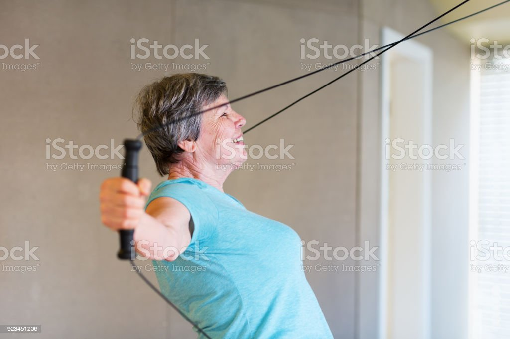 Senior woman, 83 yeas old, working out at a machine, doing strength...