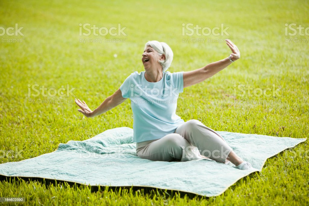 Senior woman enjoying fresh air in park stock photo