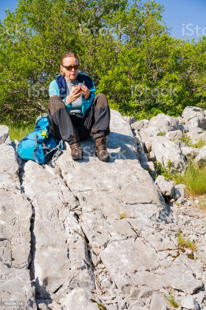 Senior woman enjoying her snack during hiking stop while sitting on rock, Zalipnik plain in Slovenia royalty-free stock photo