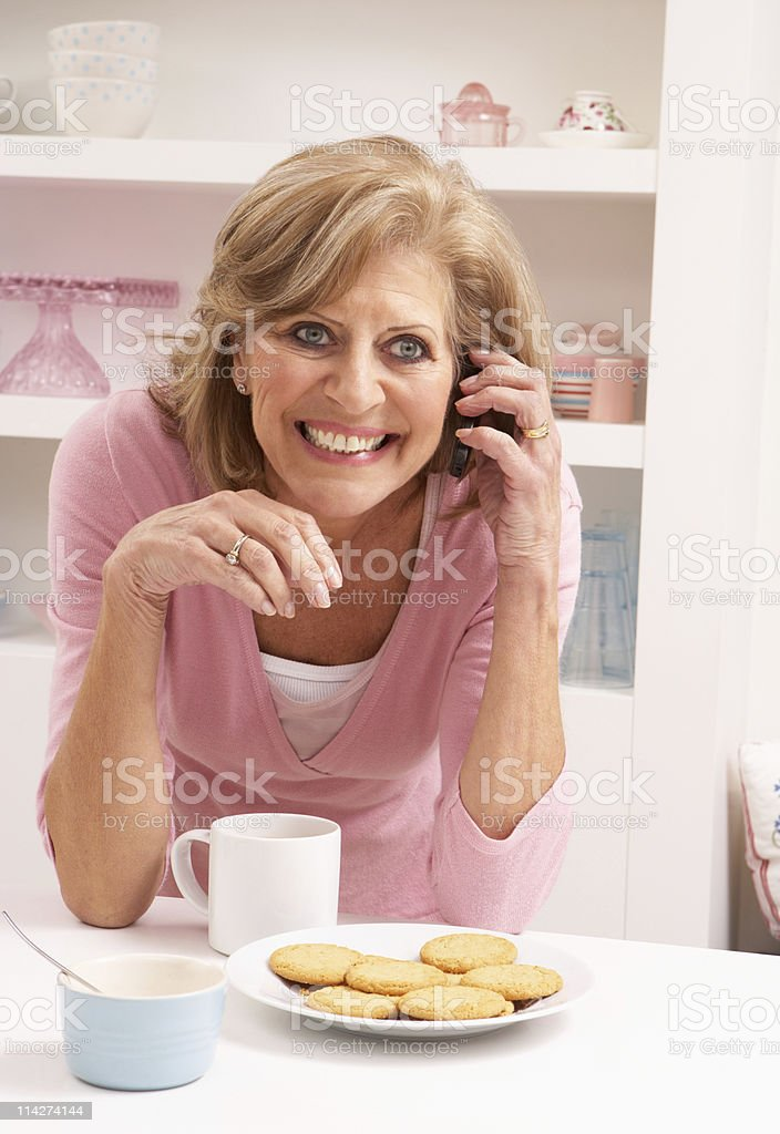 Senior Woman Enjoying Hot Drink Whilst On Phone royalty-free stock photo