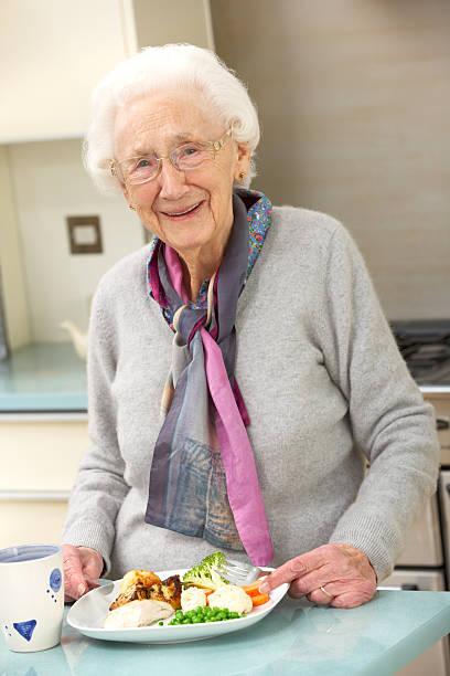 Senior woman enjoying meal in kitchen stock photo