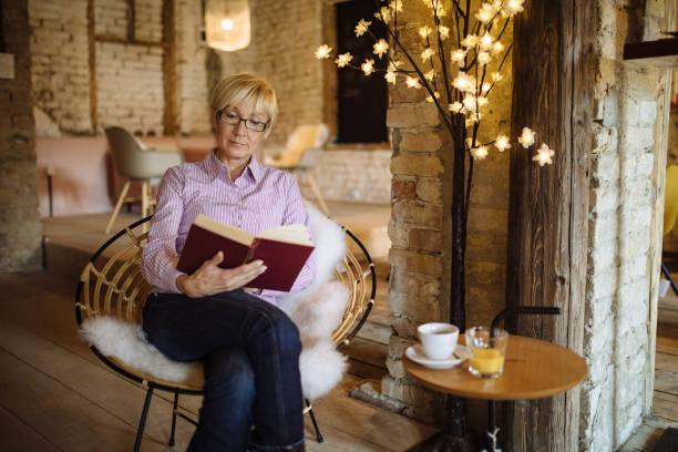 Senior woman enjoying reading a book stock photo