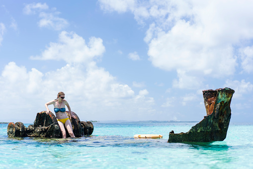 Senior woman enjoying shipwreck near Isla de  Perro island in Caribbean See