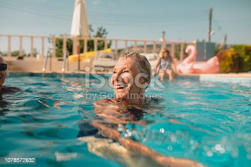 Senior woman swimming in a swimming pool while on holiday in Paphos, Cyprus. She is turning her head as she swims to laugh at her friends.