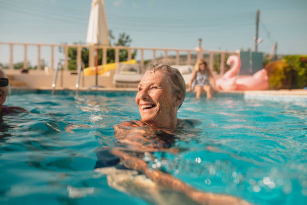 Senior Woman Enjoying Summer Vacation Senior woman swimming in a swimming pool while on holiday in Paphos, Cyprus. She is turning her head as she swims to laugh at her friends. young at heart stock pictures, royalty-free photos & images