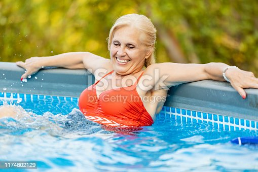 An old lady, amused, swimming to keep fit. outdoor pool with clear water and sunny day. Caucasian and smiling