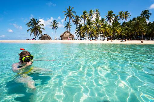 Senior woman enjoying swiming with scuba mask near Isla de  Perro island in Caribbean See
