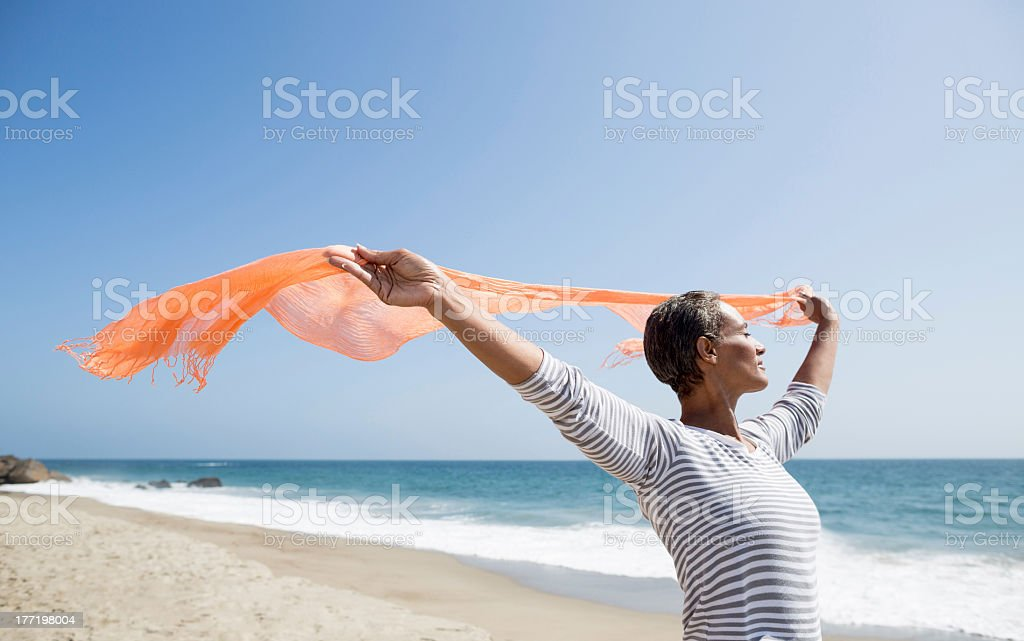 Senior woman enjoying the beach stock photo