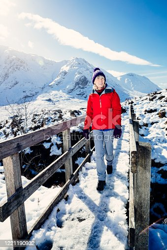 Senior woman enjoying the sunshine in a snowy Glencoe, Scotland. The trail is known as the Devil's Staircase and connects Altafeadh with Loch Leven.