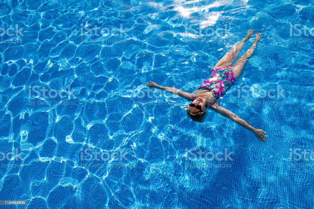 Woman on tropical holidays in the outdoor swimming pool, directly...