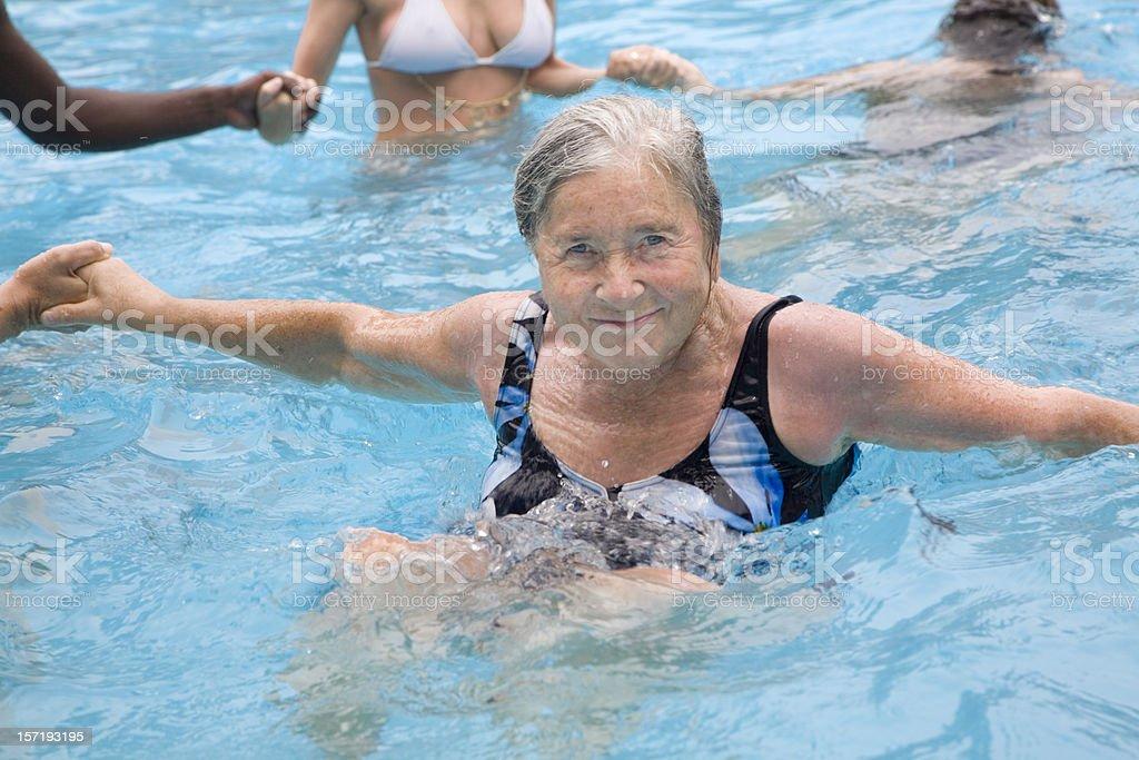 Senior woman enjoying water aerobics with young people royalty-free stock photo