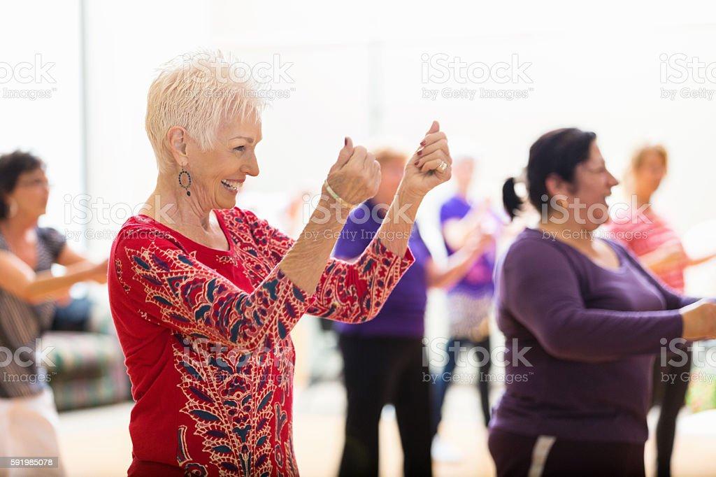Senior woman enjoys dance class stock photo