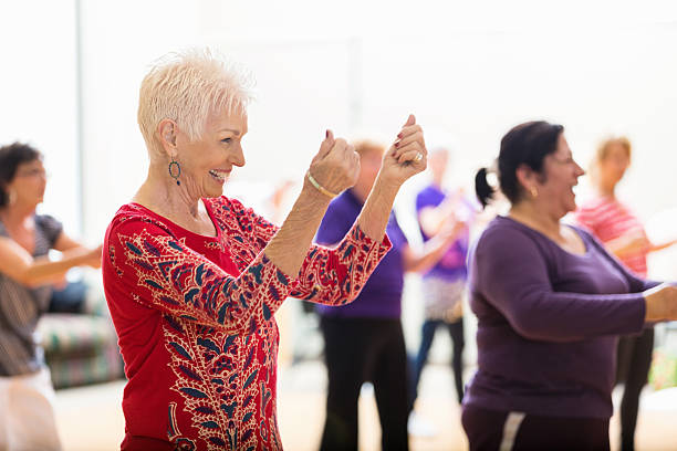 Senior woman enjoys dance class stock photo