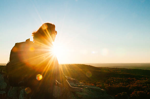 Senior Woman Enjoys Scenic Hike Mountain View Sunset Catskill Mountains This is a horizontal, color, royalty free stock photograph of a senior woman enjoying the sunset view after reaching the top of the mountain after a day hike. She rests her hands on the rocky ledge as she looks towards the bright sun that back lights her, creating a silhouette and shining a warm, sunny lens flare. The sun is setting over the autumn trees in the scenic Ulster County Catskill Mountain region near Ellenville, New York. There is copy space in the clear sky. catskill mountains stock pictures, royalty-free photos & images