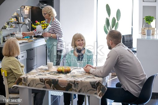 Senior woman making flower arrangment in kitchen while her friends sitting around, chatting with young man