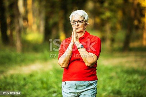 Senior woman enjoys exercise Tai Chi in the nature