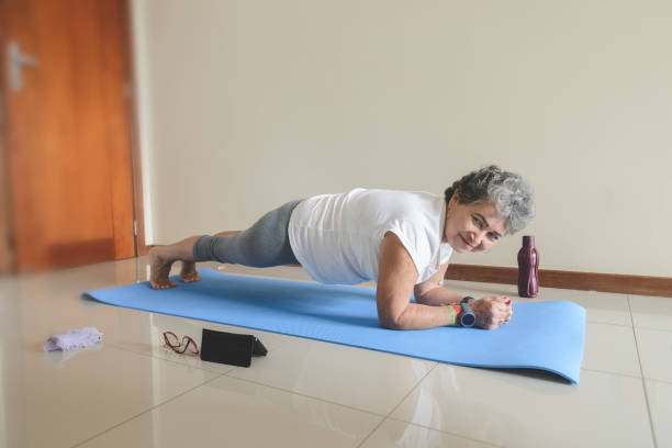 Senior woman exercising and doing plank position at home stock photo