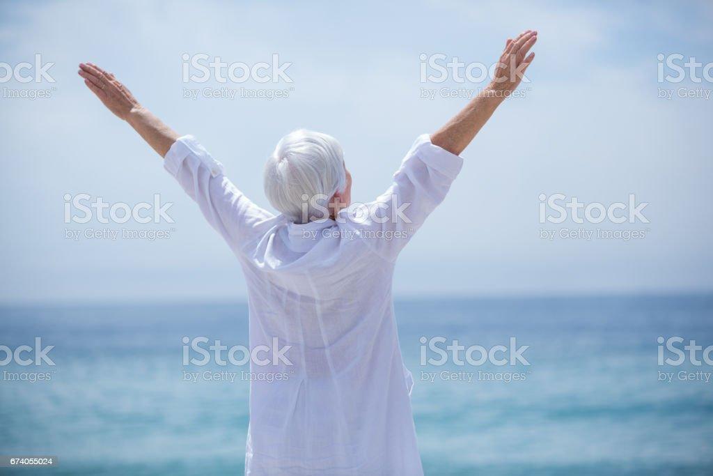Senior woman exercising at beach on sunny day royalty-free stock photo