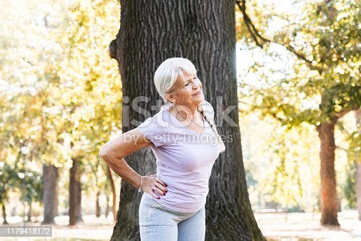 Closeup of senior woman doing fitness workout in park. Hip stretching position. painfull expresion of her face. Billboard image