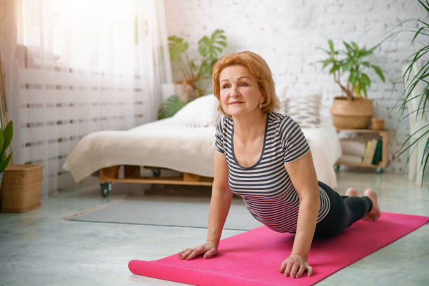 Senior woman exercising home, the concept of a healthy lifestyle, fitness and yoga stock photo