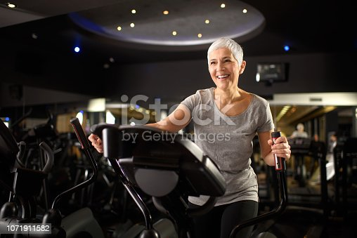 Active senior female exercising on the cross trainer machine in a health club.