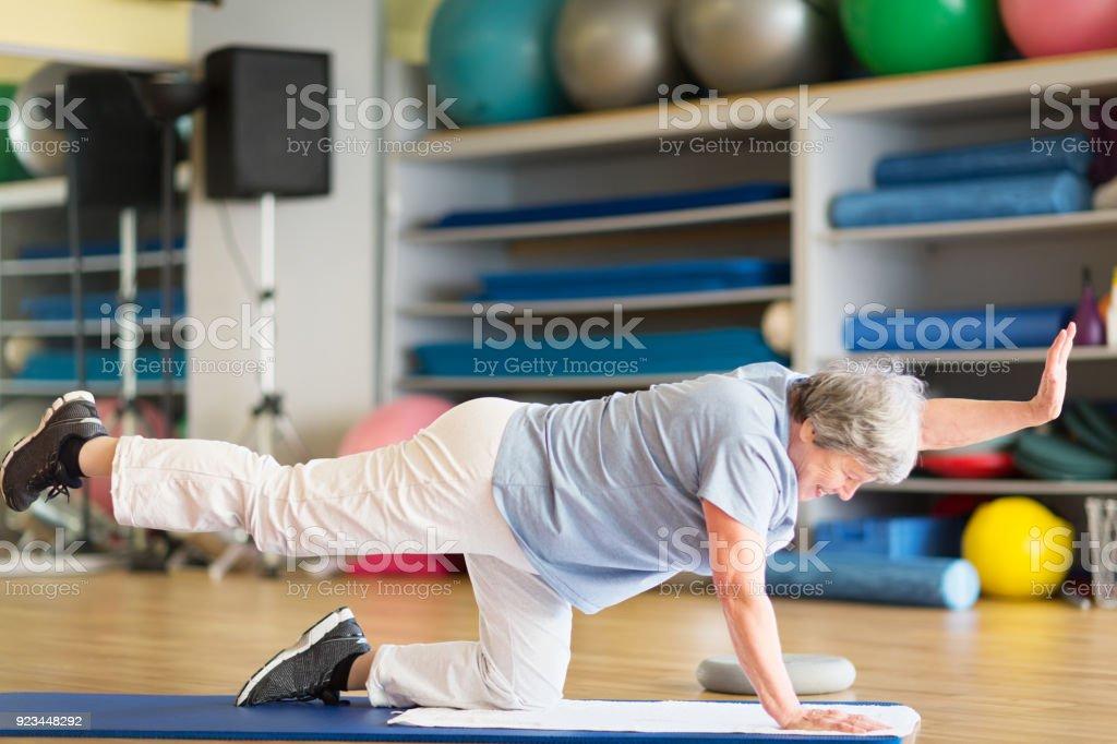 senior woman exercising in gym on mat stock photo